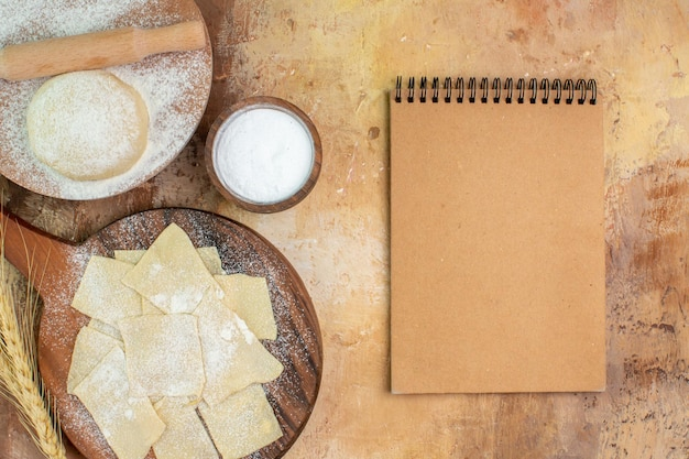 Vue de dessus des tranches de pâte crue avec de la farine sur le bureau de la crème