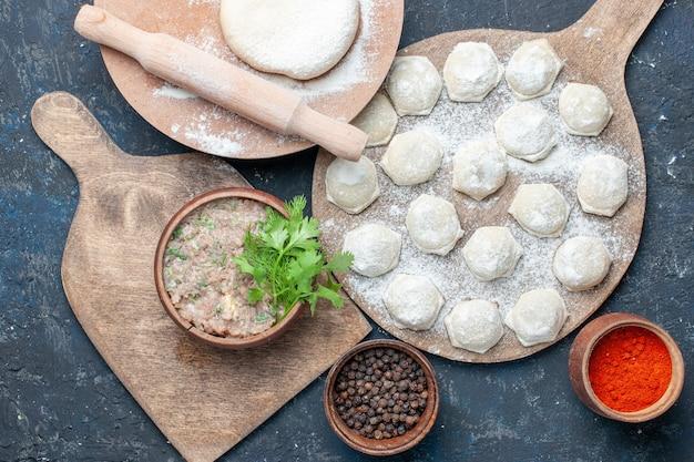 Vue de dessus des tranches de pâte farinée avec des verts de viande hachée et des poivrons sur un bureau sombre, dîner de viande crue alimentaire