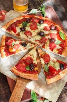 Une vue de dessus de tranches de pizza sur une planche à découper en bois