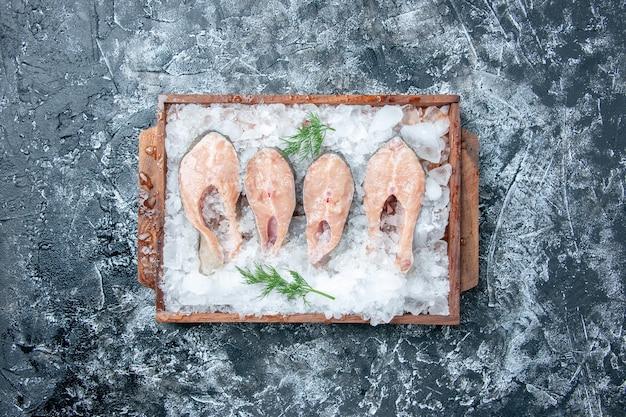 Vue de dessus des tranches de poisson cru avec de la glace sur une planche de service en bois sur fond gris