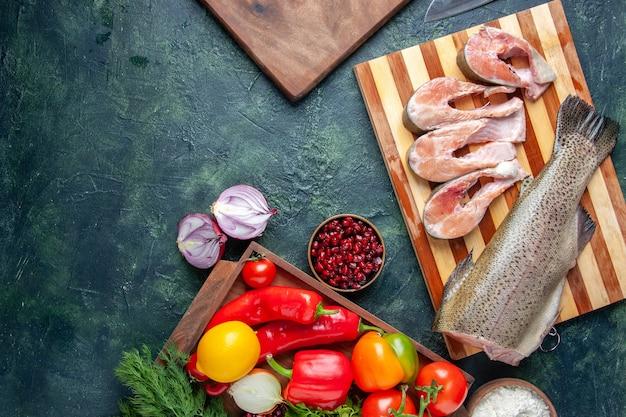 Vue de dessus des tranches de poisson cru sur une planche à découper des légumes sur une planche de service en bois sur une table de cuisine