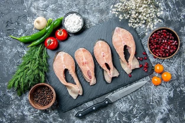 Vue de dessus des tranches de poisson cru sur tableau noir légumes couteau graines de grenade sur table