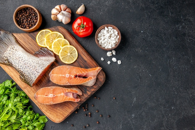 Vue de dessus tranches de poisson frais avec citron et légumes verts sur fond gris foncé salade de poisson eau viande océan mer repas dîner fruits de mer espace libre