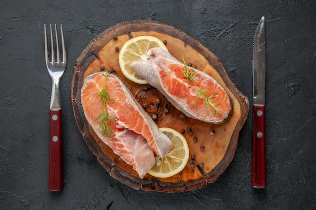 Vue de dessus des tranches de poisson frais avec du citron et des couverts sur une table sombre