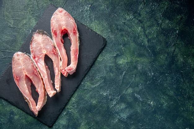 Vue de dessus des tranches de poisson frais sur fond sombre