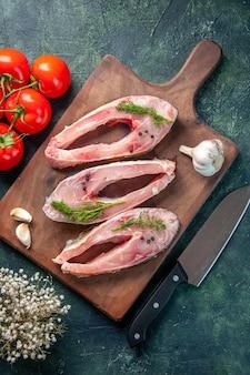 Vue de dessus des tranches de poisson frais avec des tomates sur fond bleu foncé