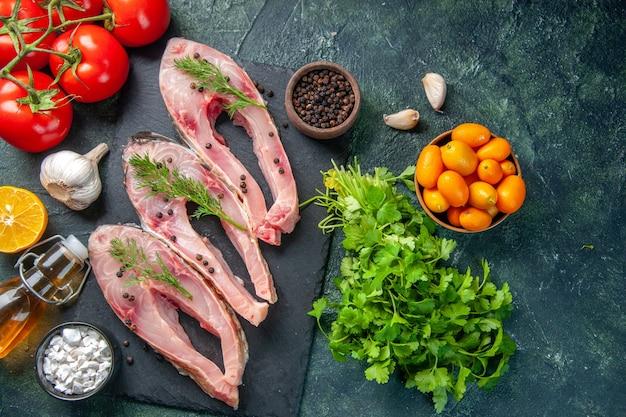 Vue de dessus des tranches de poisson frais avec des tomates rouges et des verts sur fond sombre