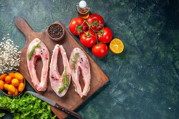 Vue de dessus des tranches de poisson frais avec des tomates et des verts sur fond sombre