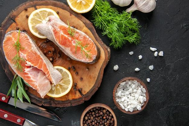 Vue de dessus des tranches de poisson frais avec des tranches de citron et de l'ail sur la table sombre