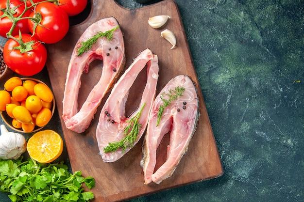 Vue de dessus des tranches de poisson frais avec des verts et des tomates sur fond sombre