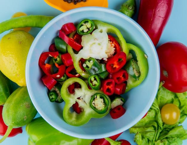 Vue de dessus des tranches de poivre dans un bol avec des légumes comme de la laitue au tomate et au citron sur la surface bleue