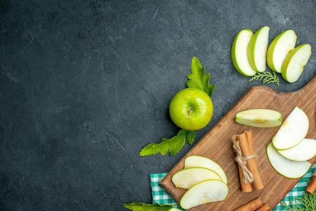 Vue de dessus des tranches de pomme et de la cannelle sur une planche à découper de la poudre de menthe séchée dans un petit bol de pomme sur fond noir