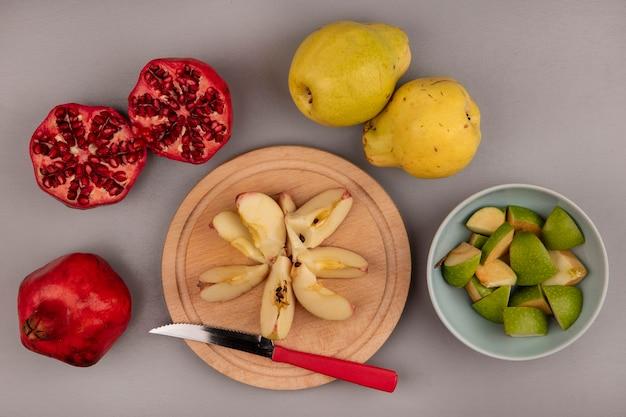 Vue de dessus de tranches de pommes fraîches hachées sur une planche de cuisine en bois avec un couteau avec des grenades et des coings isolés