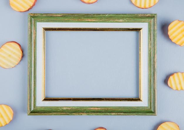 Vue de dessus des tranches de pommes de terre autour du cadre sur une surface bleue avec copie espace