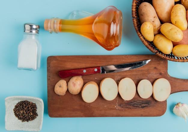 Vue de dessus des tranches de pommes de terre et couteau sur une planche à découper avec des entiers dans le panier beurre sel et poivre noir et ail sur bleu