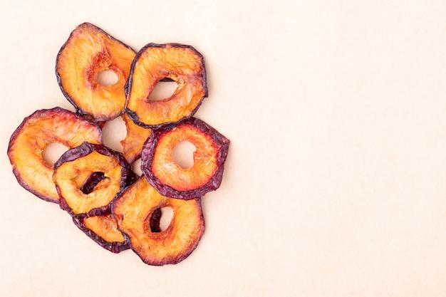 Vue de dessus des tranches de prune séchées isolé sur fond de texture de papier brun avec copie espace