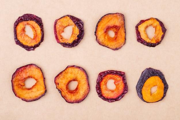 Vue de dessus des tranches de prune séchées isolé sur fond de texture de papier brun