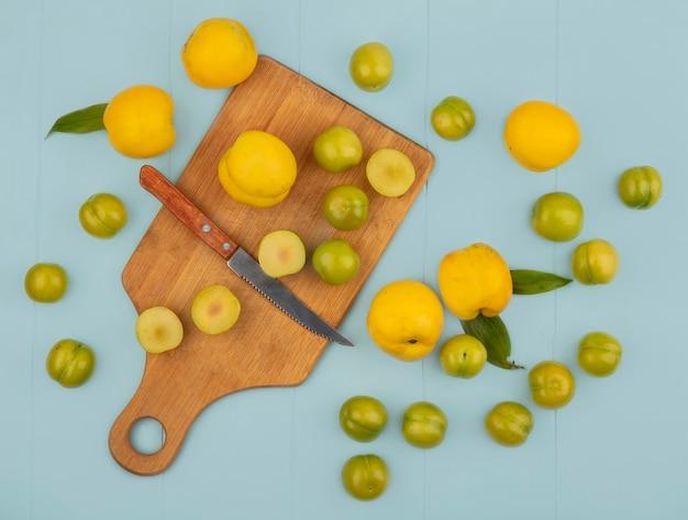 Vue de dessus des tranches de prunes cerises vertes sur une planche de cuisine en bois avec un couteau avec des pêches jaunes isolé sur fond bleu