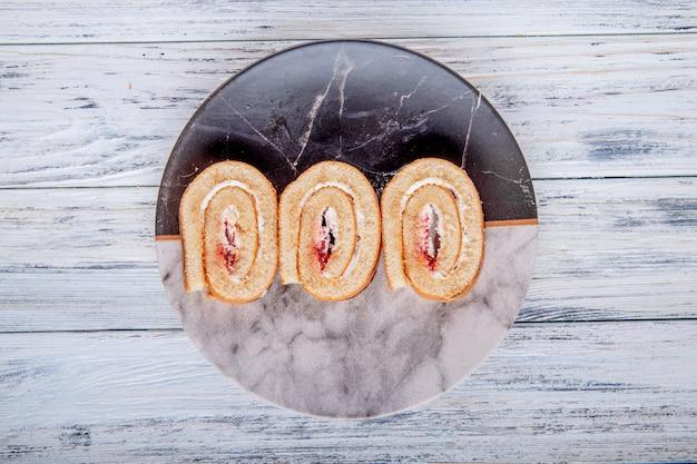Vue de dessus des tranches de rouleau suisse avec de la crème fouettée et de la confiture de framboise sur une plaque sur fond rustique