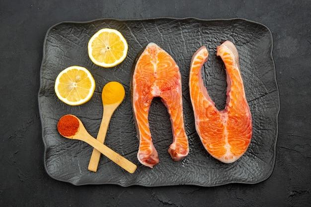 Vue de dessus des tranches de viande fraîche à l'intérieur de la plaque avec du citron sur fond sombre
