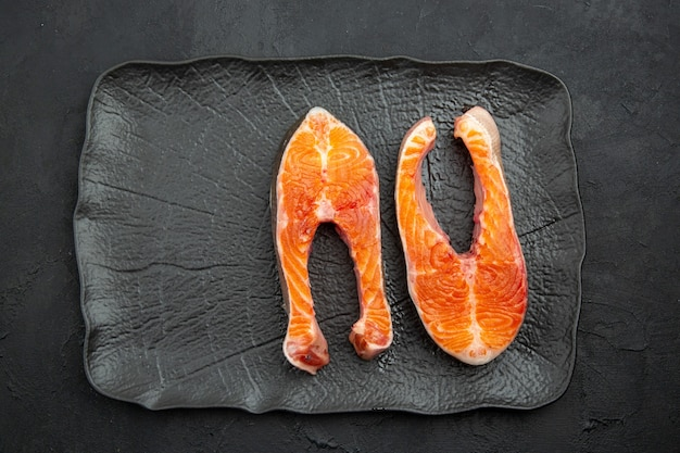 Vue de dessus des tranches de viande fraîche à l'intérieur de la plaque sur fond sombre
