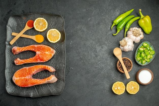 Vue de dessus des tranches de viande frites avec des assaisonnements et des légumes frais sur fond sombre