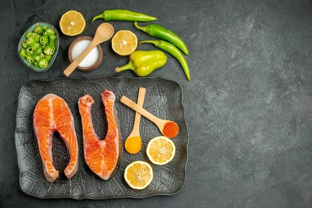 Vue de dessus des tranches de viande frites avec des poivrons et du citron sur fond sombre
