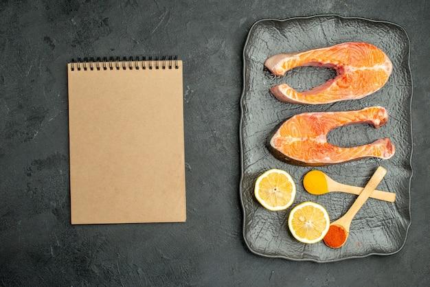 Vue de dessus des tranches de viande frites avec des poivrons et du citron sur un sol sombre