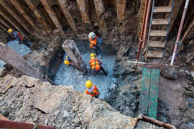 Vue de dessus, le travailleur masculin était en béton avec une machine à plâtre creusée dans un trou avec une pelle rétrocaveuse à l'intérieur d'espaces confinés. il y avait de la terre autour.