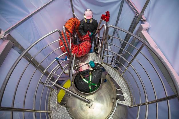 Vue de dessus travailleur masculin monter les escaliers dans le réservoir zone chimique inoxydable espace confiné ventilateur de sécurité air frais