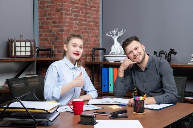 Vue de dessus de travailleurs qualifiés souriants et motivés qui m'appellent et font un geste correct au bureau