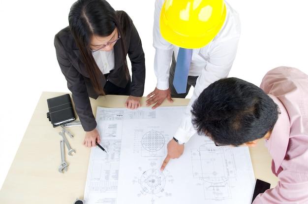 Vue de dessus de trois architectes se tenant devant la table et discutant d'un projet de conception.