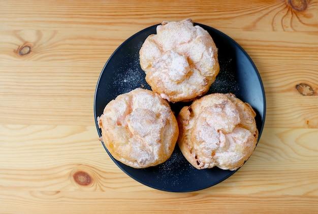 Vue de dessus de trois choux à la crème profiterole saupoudrés de sucre glace à la fraise