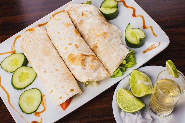 Vue de dessus de trois enveloppements de tortillas mexicaines avec tequila, citron et sel sur table en bois
