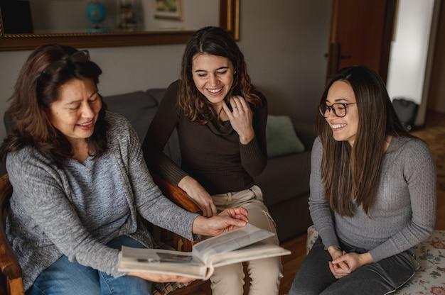 Vue de dessus trois femmes, mère et filles à la recherche d'un livre de souvenirs. ensemble, concept de famille.