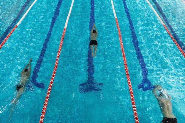 Vue de dessus de trois nageurs masculins