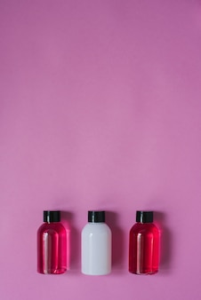 Vue de dessus de trois petites bouteilles de produits de soin pour le corps et les cheveux blancs et cramoisis sur un fond rose