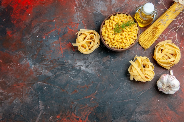 Vue de dessus de trois portions de spaghettis et de pâtes papillon non cuites dans un bol brun et une bouteille d'huile d'ail citron vert oignon sur table de couleurs mixtes