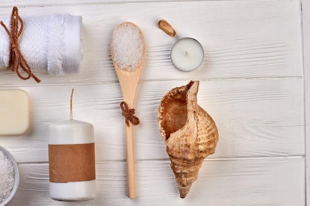 Vue de dessus des trucs de beauté spa sur un bureau en bois blanc. bougie avec coquillage et cuillère. disposition à plat des accessoires.