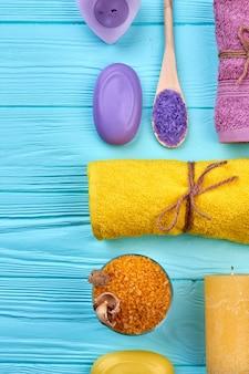 Vue de dessus des trucs de salle de bain spa sur un bureau en bois bleu. serviette jaune roulée avec du savon et du sel.