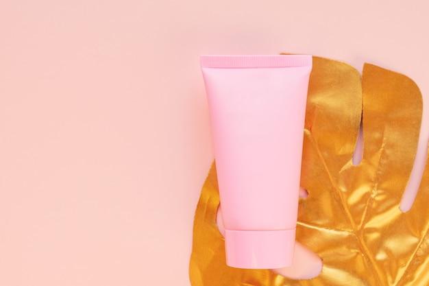 Vue de dessus d'un tube rose de maquette de crème avec une feuille de monstera dorée sur fond rose. paquet de cosmétiques sans marque.