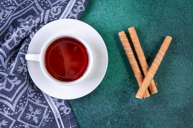 Vue de dessus des tubes sucrés avec une tasse de thé sur vert