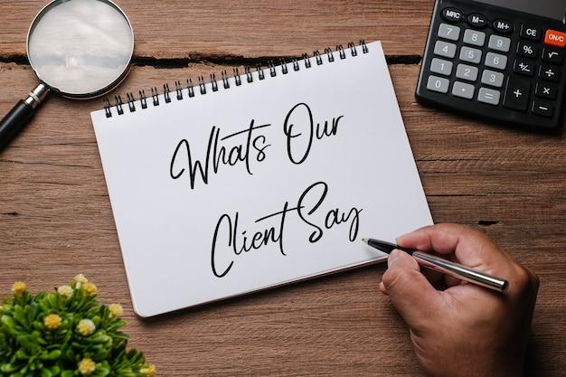 Vue de dessus de l'usine, des lunettes, de l'horloge et de la main tenant un stylo écrivant ' ce que nos clients disent ' sur un carnet de notes sur fond de bois.