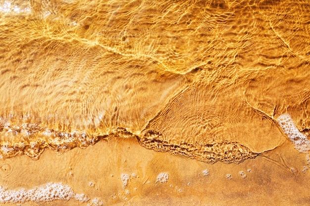 Vue de dessus de la vague près de la plage de sable fin.