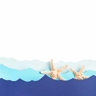 Vue de dessus des vagues de l'océan en papier avec des étoiles de mer