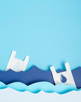 Vue de dessus des vagues de l'océan en papier avec des sacs en plastique
