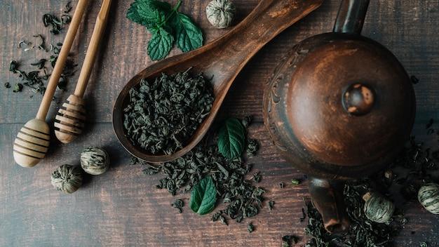 Vue de dessus variété d'herbes à thé et de bâtonnets de miel