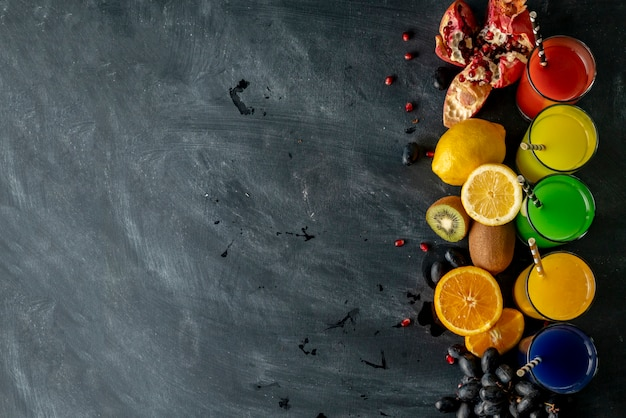 Vue de dessus de la variété de jus de fruits frais, différents fruits autour, espace de copie pour votre texte sur un tableau noir