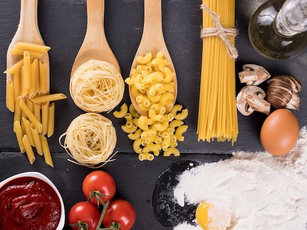 Vue de dessus d'une variété de pâtes crues non cuites à côté d'œufs dans de la farine, de la sauce tomate, des tomates fraîches, des champignons coupés et de l'huile de tournesol