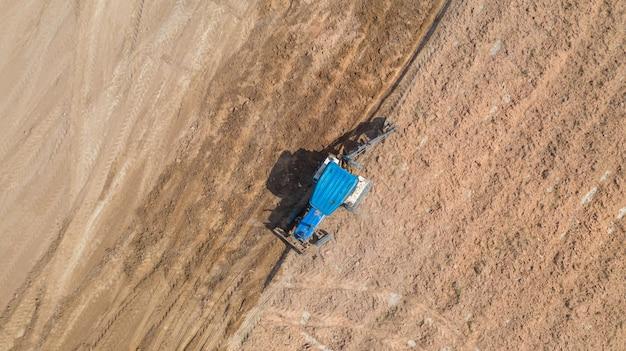 Vue de dessus des véhicules de tracteur agricole travaillant au champ